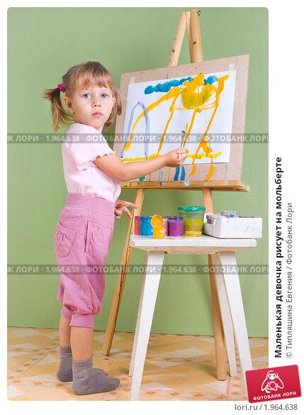 Маленькая девочка рисует на мольберте