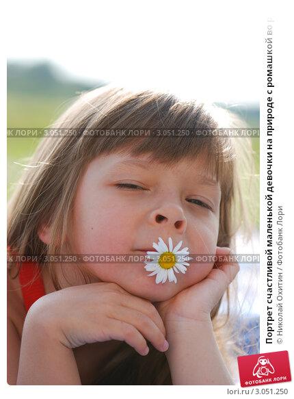 Портрет счастливой маленькой девочки на природе с ромашкой во рту