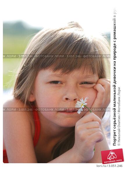 Портрет серьёзной маленькой девочки на природе с ромашкой в руке
