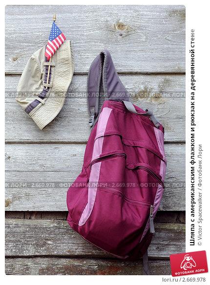 Шляпа с американским флажком и рюкзак на деревянной стене, фото 2669978.