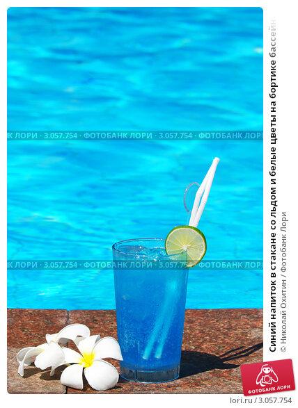 Синий напиток в стакане со льдом и белые цветы на...