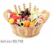 Купить «Плетеная соломенная корзинка с конфетами и другими сладостями, на белом фоне», фото № 83718, снято 9 января 2007 г. (c) Александр Паррус / Фотобанк Лори