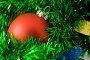 Красный елочный шар на фоне зеленой мишуры, фото № 127330, снято 6 ноября 2007 г. (c) Наталья Герасимова / Фотобанк Лори