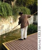 Купить «Мужчина вылавливает грязь из водоема при помощи сачка», фото № 133318, снято 19 сентября 2018 г. (c) Вера Тропынина / Фотобанк Лори