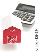 Красный дом и калькулятор на белом фоне. Стоковое фото, фотограф Останина Екатерина / Фотобанк Лори