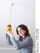 Купить «Девушка  вкручивает в патрон  апельсин вместо лампочки», фото № 155278, снято 5 декабря 2007 г. (c) Ирина Мойсеева / Фотобанк Лори