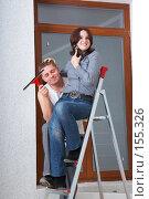 Купить «Молодой человек отдыхает от работы, девушка болтает по телефону, сидя на стремянке», фото № 155326, снято 5 декабря 2007 г. (c) Ирина Мойсеева / Фотобанк Лори
