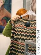 Купить «Девушка в магазине одежды выбирает платье», фото № 176894, снято 13 октября 2007 г. (c) Наталья Белотелова / Фотобанк Лори