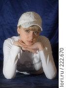 Купить «Девушка в белой кепке лежит на синем фоне», фото № 222670, снято 25 февраля 2008 г. (c) Арестов Андрей Павлович / Фотобанк Лори