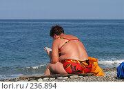 Купить «Полная женщина в ярком купальнике читает газету на берегу моря. Абхазия», фото № 236894, снято 25 августа 2006 г. (c) Виктор Филиппович Погонцев / Фотобанк Лори