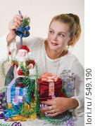 Купить «Женщина с подарками к новому году держит в руках колокольчик», фото № 549190, снято 7 ноября 2008 г. (c) Ольга Кедрова / Фотобанк Лори