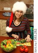 Купить «Девушка в новогоднем колпаке режет овощи для салата», эксклюзивное фото № 583282, снято 23 ноября 2008 г. (c) Оксана Гильман / Фотобанк Лори