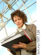 Купить «Молодая девушка, подписывающая документы», фото № 597126, снято 15 ноября 2008 г. (c) Дмитрий Яковлев / Фотобанк Лори