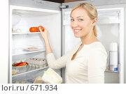 Купить «Девушка берет помидоры из холодильника», фото № 671934, снято 19 октября 2008 г. (c) Raev Denis / Фотобанк Лори