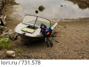 Мальчик у лодки во время отлива (2008 год). Редакционное фото, фотограф Эдуард Финовский / Фотобанк Лори