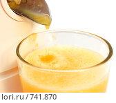 Апельсиновый сок вытекает из соковыжималки. Стоковое фото, фотограф nikolay uralev / Фотобанк Лори