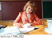 Учитель в классе за проверкой тетрадей. Стоковое фото, фотограф Ирина Золина / Фотобанк Лори