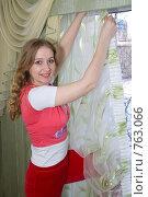 Купить «Улыбающаяся девушка вешает шторы», фото № 763066, снято 21 марта 2009 г. (c) Тимур Ахмадулин / Фотобанк Лори
