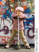 Хорошенькая маленькая девочка со скутером возле стены, разрисованной граффити. Стоковое фото, фотограф Sergii Korshun / Фотобанк Лори