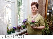 Купить «Женщина с цветущими комнатными фиалками», фото № 847738, снято 25 апреля 2009 г. (c) Галина Лукьяненко / Фотобанк Лори