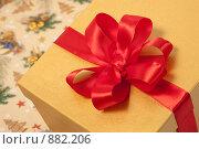 Купить «Новогодний подарок в золотистой коробке с красным атласным бантом», фото № 882206, снято 24 мая 2009 г. (c) Архипова Мария / Фотобанк Лори