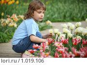 Купить «Задумавшаяся девочка у клумбы», фото № 1019106, снято 10 мая 2009 г. (c) Losevsky Pavel / Фотобанк Лори