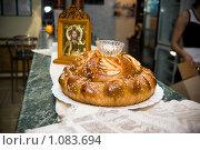 Свадебный румяный хлеб с солью лежит тарелке а на фоне православной иконы. Стоковое фото, фотограф Полина Бублик / Фотобанк Лори