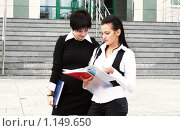 Две девушки - офисные работники - рассматривают документы на фоне офисного здания. Стоковое фото, фотограф Ирина Золина / Фотобанк Лори