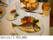 Купить «Жареная рыба с овощным гарниром на тарелке на столе в ресторане», фото № 1163486, снято 25 сентября 2008 г. (c) Константин Бредников / Фотобанк Лори