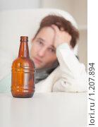 Грустный молодой человек отрешенно смотрит на бутылку пива - похмелье. Стоковое фото, фотограф pzAxe / Фотобанк Лори
