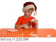 Купить «Мальчик в красном колпаке вырезает новогоднюю снежинку», фото № 1223394, снято 18 ноября 2009 г. (c) Юлия Кашкарова / Фотобанк Лори