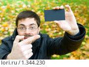 Купить «Молодой мужчина держит в руках чёрную визитку», фото № 1344230, снято 10 октября 2009 г. (c) Анна Лурье / Фотобанк Лори
