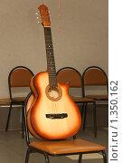 Купить «Акустическая гитара на стуле, ожидающая артиста», фото № 1350162, снято 30 декабря 2009 г. (c) Сергей Плюснин / Фотобанк Лори