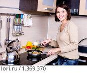 Купить «Молодая девушка готовит еду на кухне», фото № 1369370, снято 21 декабря 2009 г. (c) Валуа Виталий / Фотобанк Лори