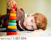 Ребенок мальчик собирает цветную пирамидку на диване. Стоковое фото, фотограф Анна Макеичева / Фотобанк Лори