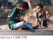 Мальчик смотрит, как мужчина плетет украшение из бисера (2009 год). Редакционное фото, фотограф Дмитрий Ващенко / Фотобанк Лори