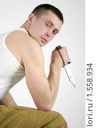 Молодой мужчина с ножом в руке на белом фоне. Стоковое фото, фотограф Федор Болба / Фотобанк Лори