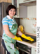 Молодая женщина моет плиту на кухне. Стоковое фото, фотограф Ирина Карлова / Фотобанк Лори