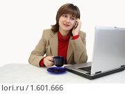 Купить «Девушка за ноутбуком пьёт кофе и разговаривает по телефону», фото № 1601666, снято 31 января 2010 г. (c) Alechandro / Фотобанк Лори