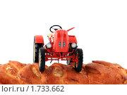 Игрушечный трактор на свежей булке. Стоковое фото, фотограф Nikiandr / Фотобанк Лори
