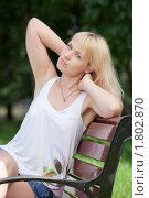 Блондинка сидит с поднятыми руками на скамейке в парке. Стоковое фото, фотограф Sergii Korshun / Фотобанк Лори