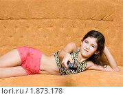 Купить «Очаровательная девочка с пультом на шикарном диване», фото № 1873178, снято 23 июля 2018 г. (c) Яна Гуляновская / Фотобанк Лори