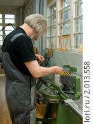 Мастер-багетчик работает за станком по изготовлению рам.Багетная мастерская. Стоковое фото, фотограф игорь иванов / Фотобанк Лори