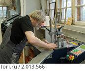 Мастер-багетчик работает на станке по соединению элементов рамы. Багетная мастерская. Стоковое фото, фотограф игорь иванов / Фотобанк Лори
