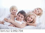 Купить «Счастливая семья на белой кровати в спальне», фото № 2092734, снято 30 сентября 2010 г. (c) Raev Denis / Фотобанк Лори