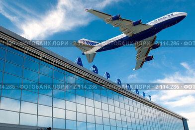 Самолет летит над зданием аэропорта