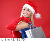 Девушка в костюме Санта-Клауса на красном фоне. Стоковое фото, фотограф Андрей Липко / Фотобанк Лори