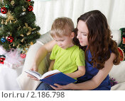Купить «Мама с сыном читают книгу возле новогодней елки», фото № 2186798, снято 9 ноября 2010 г. (c) Андрей Липко / Фотобанк Лори