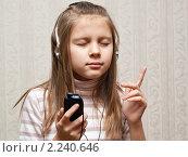 Девочка-подросток слушает музыку в наушниках по сотовому телефону. Стоковое фото, фотограф Игорь Низов / Фотобанк Лори