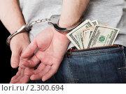 Экономические преступления, коррупция, взятки - стальные наручники на руках за спиной мужчины и деньги в кармане его брюк. Стоковое фото, фотограф Илья Андриянов / Фотобанк Лори